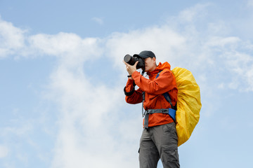 Picture of male photographer with camera and backpack