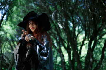 Image of young witch in gloomy forest