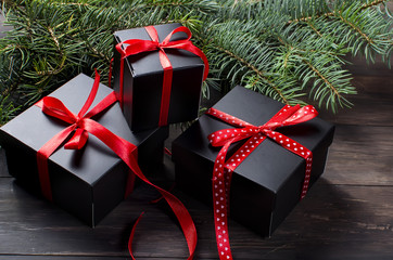 Black christmas  gift  box with red ribbon and fir branches