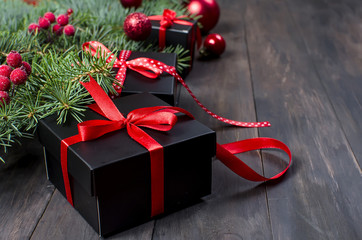 Black and red  christmas  gift  box with red ribbon and fir branches
