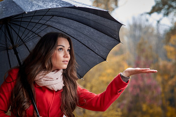 A girl in a red coat with a black umbrella in the rain in the autumn