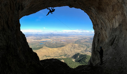 Climber in high mountains at a cave exit
