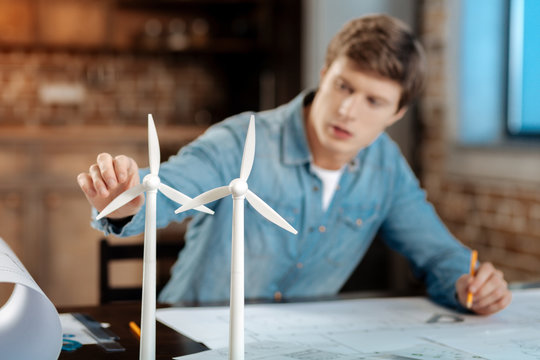 Young engineer touching wind turbine blade