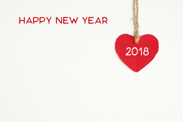 Red fabric heart shape with 2018 word hanging on the clothesline over white wall background, new year template