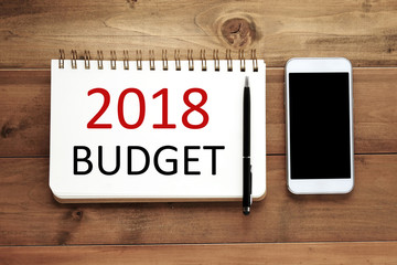Smart phone and 2018 budget on note book paper on wood background, business financial and technology concept