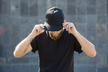 Hipster handsome male model with beard  wearing black blank  baseball cap  with space for your logo