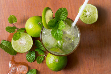 Fresh Mojito cocktail with fresh green limes, mint and ice on wooden background.