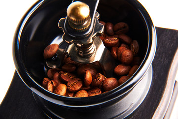 Manual coffee grinder./A hand grinder with coffee beans.