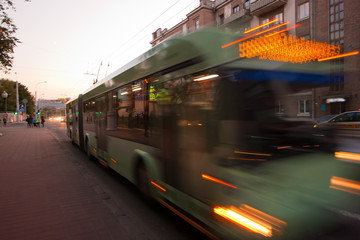 The motion of a blurred trolleybus on the street at dusk