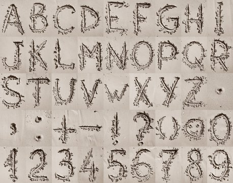 Handwritten English alphabet, numbers and mathematical symbols on the sand.