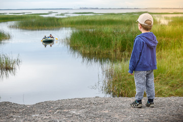 a little boy looks from the shore to a fishing boat overlooking the sea
