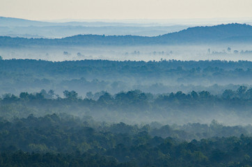 Fog flows through the valleys and hills below a scenic overlook in the Talladega National Forest in Alabama, USA