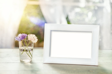 Empty frame mockup with flowers in glass