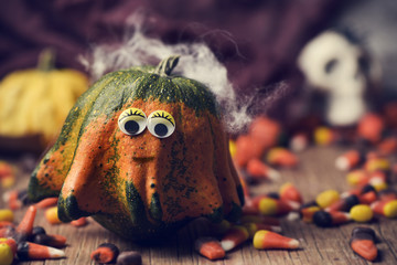 pumpkin with funny eyes, candies and skull