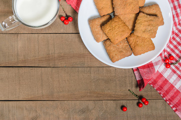 Biscuits, milk, red napkin, Christmas decor with free space for text.