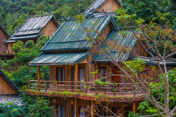 Wooden bamboo houses in the jungle. Sanya Li and Miao Village. Hainan, China.