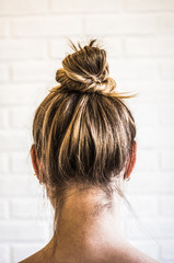 Head of a young woman from behind. Hair bun