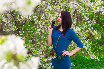 A young woman with retro camera photographing a blue dress