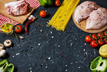 Pasta ingredients. Chicken breasts, Cherry tomatoes, spaghetti pasta, bacon and mushrooms on the stone table. space for text.
