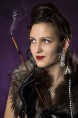 beautiful female retro style portrait with cigarette on purple background