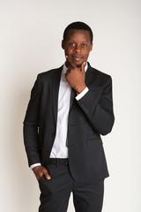 Powerful black businessman standing in suit, straightens tie