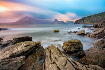 Moody dramatic sky over the Cuillin Range with interesting shaped rocks in foreground. Taken at Elgol, Scotland, UK.