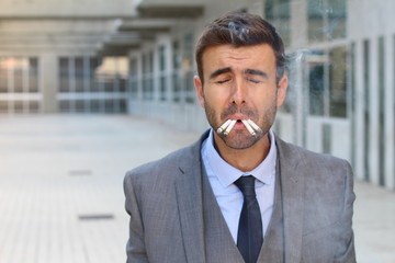 Stressed out businessman smoking four cigarettes at the same time