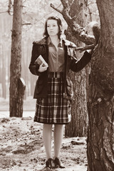 A girl with a book in a forest near a tree. Postprocessing.