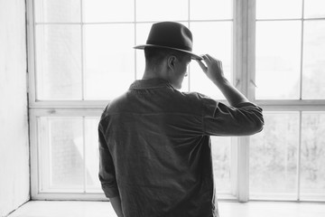 Man holding his hat in front of big window
