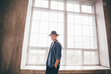 Man dressed in hat and denim shirt standing in front of window