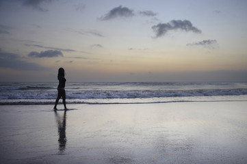 attractive african american black woman walking on sunset beach enjoying water and sand relaxed