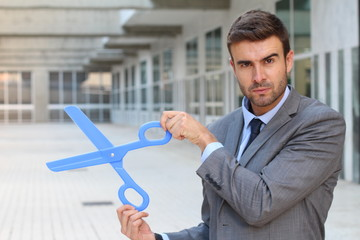 Businessman holding a pair of scissors