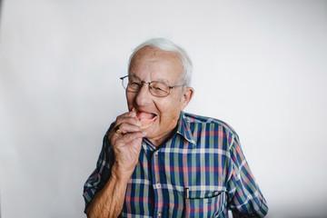 Playful senior man removing dentures and laughing