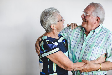 Senior couple enjoying each other in front of white background