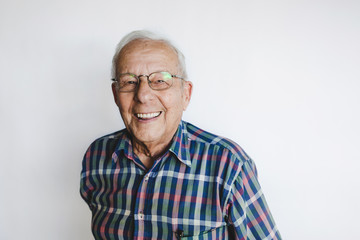 Happy senior man looking at camera on white background