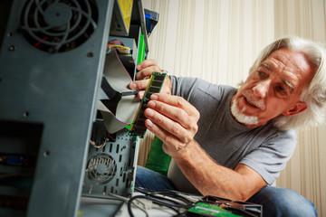 Senior Man Assembling A Desktop Computer