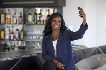 happy black afro american woman in casual elegant clothes taking selfie portrait photo with mobile phone