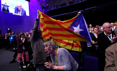 Delgates hold a Catalan flag at the Scottish National Party conference in Glasgow