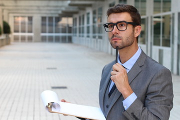 Businessman thinking while taking notes