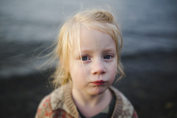 Portrait of a little girl against the dark water