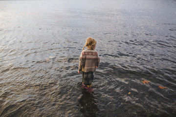 A little girl stands fully dressed in Cold Water at Sunset