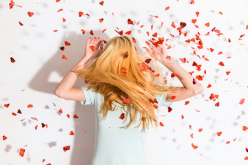 Heart-shaped confetti falling over a blonde girl
