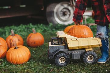 Cute little boy in plaid jacket pushing dumptruck at pumpkin farm
