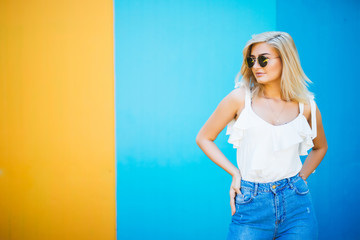 Pretty young woman blond style with against the colorful wall.
