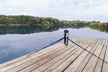 Digital camera standing on a tripod on a wooden platform near the lake