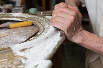 Manos de maestro restaurador trabajando con gubia.