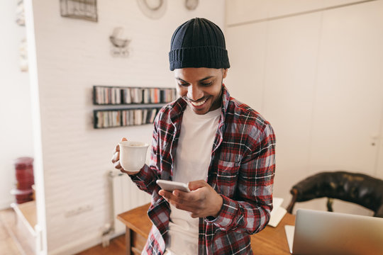 Smiling man holding a coffee using phone at home office.