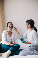 Two female friends having beauty treatment in their home