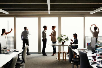 Profile silhouette of business team close to windows mulittasking