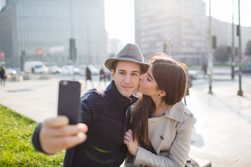Young couple taking a selfie with kiss
